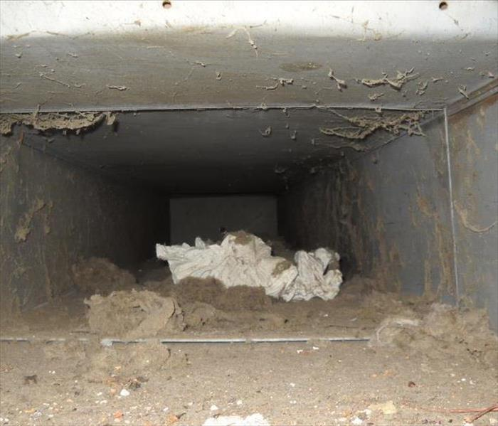 A photo of an air duct with a lot of dust and debri
