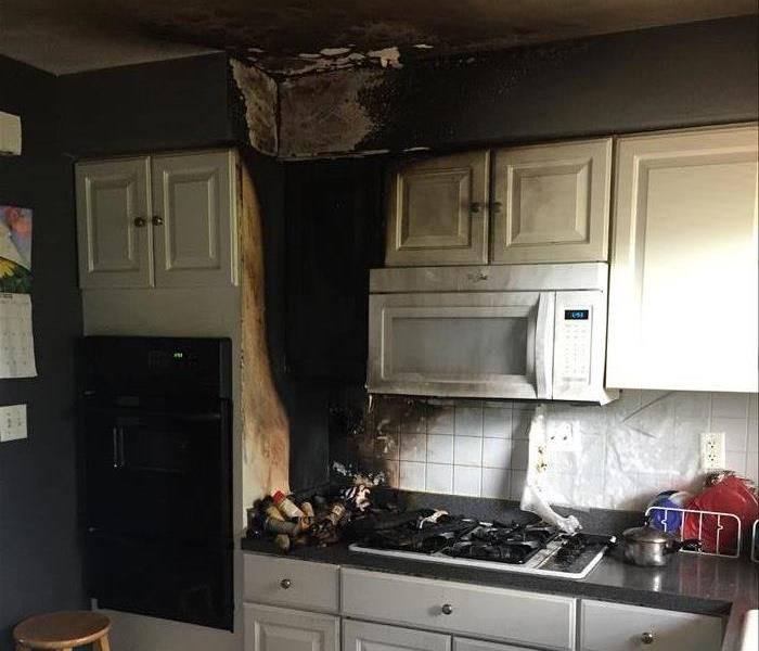 Kitchen cabinets, a microwave, and ceiling with fire and smoke damage