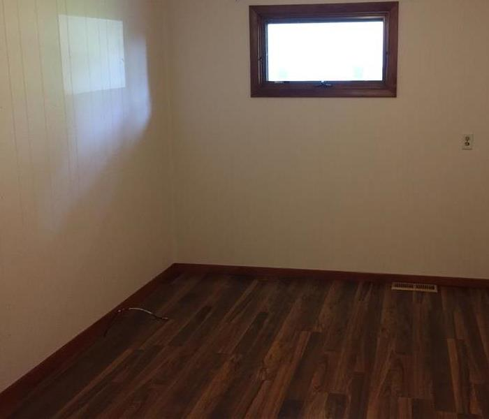 A bedroom with brand new hardwood floors
