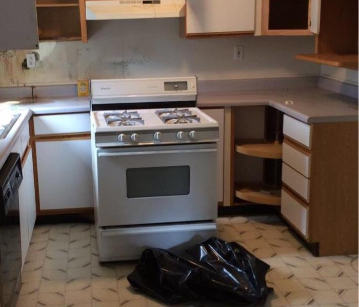 A kitchen with a trash bag and a stove moved away from cabinets. The cabinets are open.