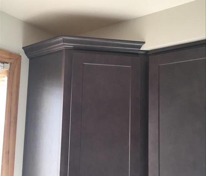 brand new dark wood cabinets in a kitchen