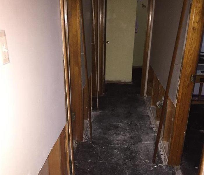 A hallway with drywall and  flooring ripped up from water damage.